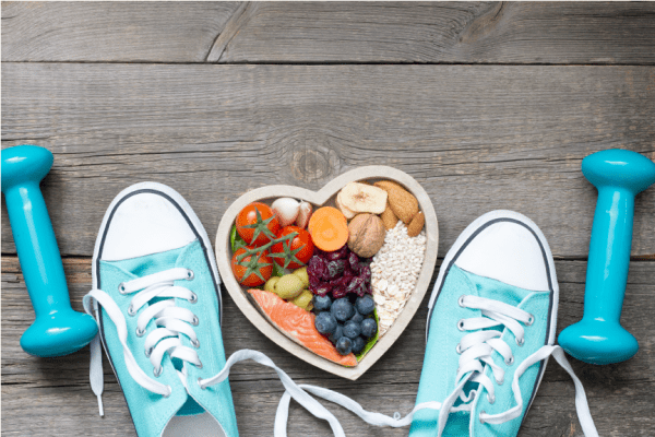 pair of sky blue converses bordering a heart-shaped bowl full of healthy foods