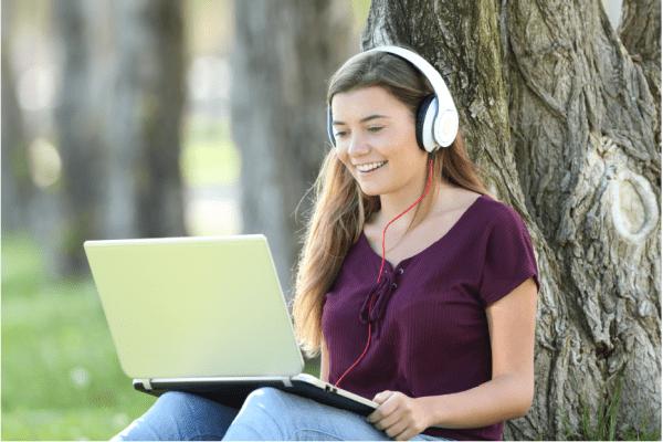 woman interacting with computer via headphones