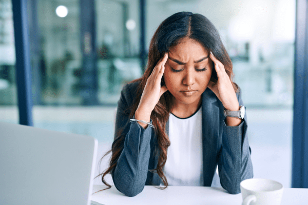 woman with hands to temples looking stressed