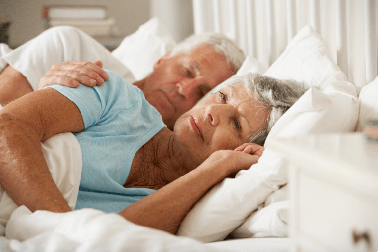 two people sleeping in bed