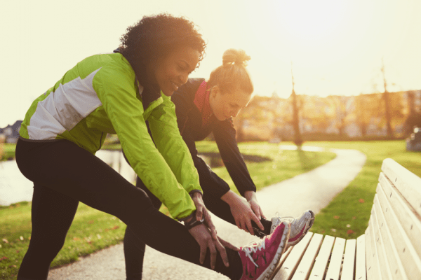 two women stretching before a run