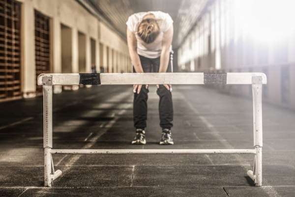 Woman standing in front of a jumping hurdle with her hands on her knees looking at the ground
