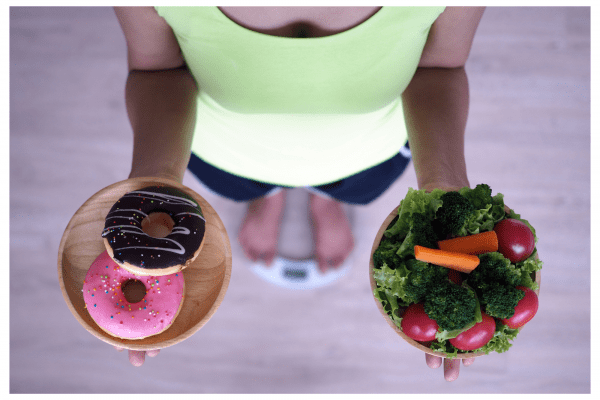 Woman holding a plate of donuts in one hand and salad in the other