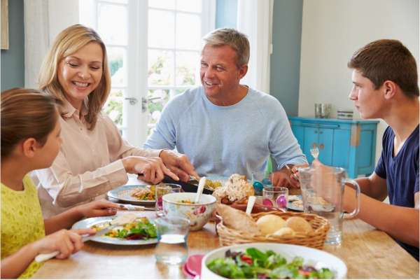 family of four at dinner table eating chicken and salad, smiling.