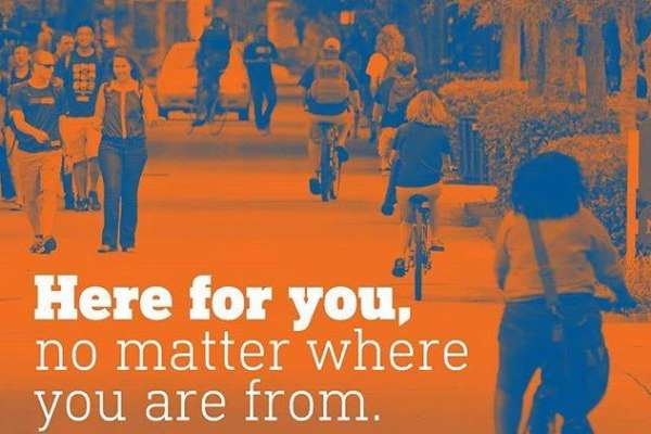 orange and blue image of people biking and walking along boulevard with text here for you no matter where you are from