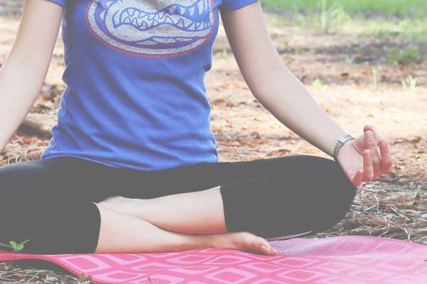woman wearing a gator t-shirt and meditating seated outdoors