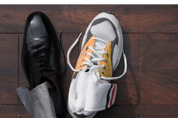 Dress shoe next to a sneaker