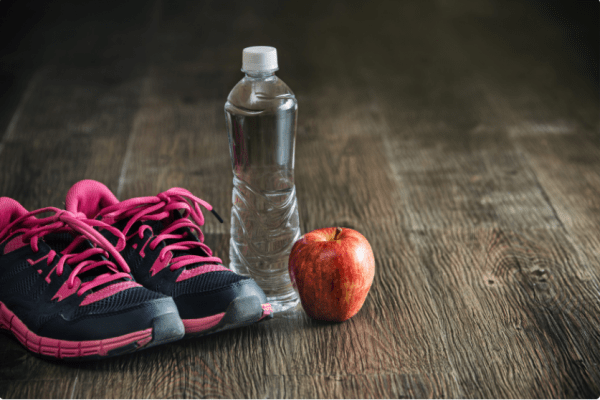 sneakers, water bottle, and apple sitting on wooden floor