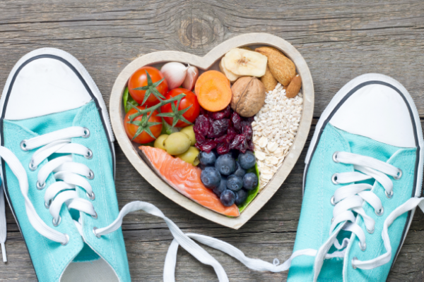 image of light blue sneakers and dumbbells surrounding heart-shaped bowl of fruits and other nutritious foods