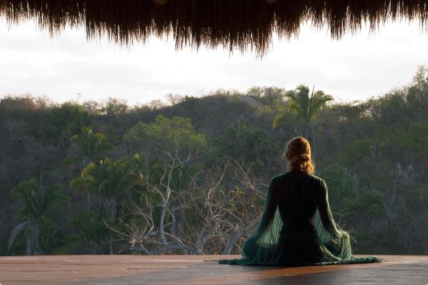 woman meditating in jungle setting, facing away