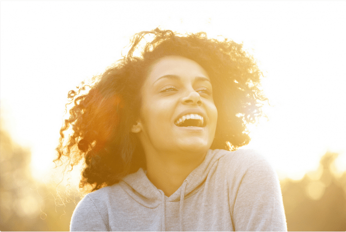 curly-haired woman laughing with golden glow around her