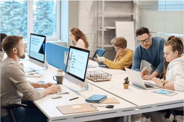 group of people sitting around a table working on different projects on the computer