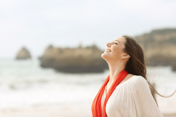 woman smiling, eyes closed, face to the sky, in a beach setting