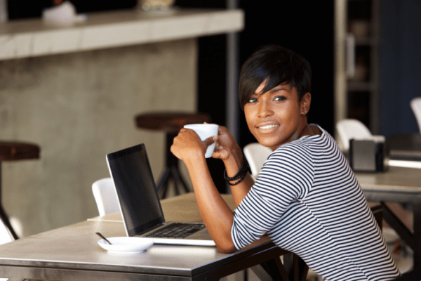 woman holding a cup of coffee, seated in front of laptop, looking at viewer