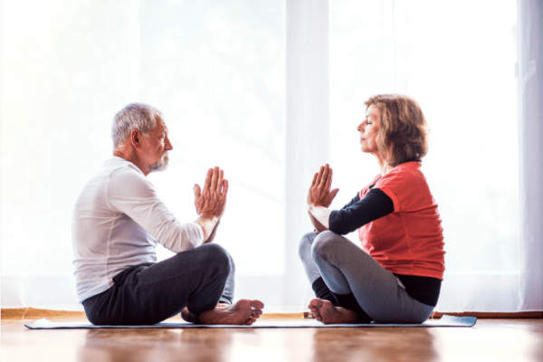 two people seated facing each other meditating with legs crossed and hands folded