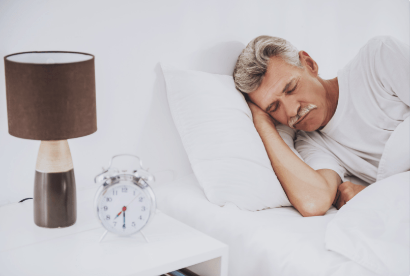 man with gray hair and mustache sleeping with an alarm clock and lamp on bedside table