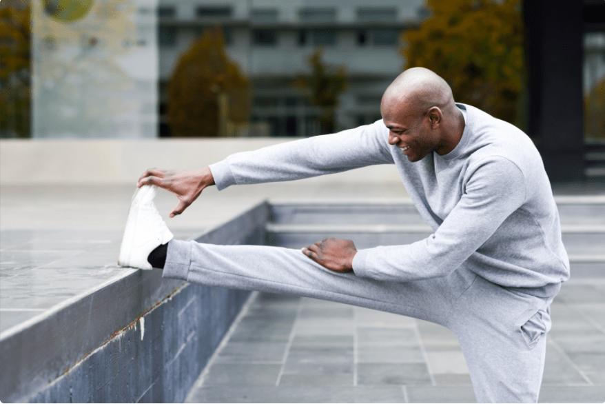 man stretching with leg up on wall reaching for toes
