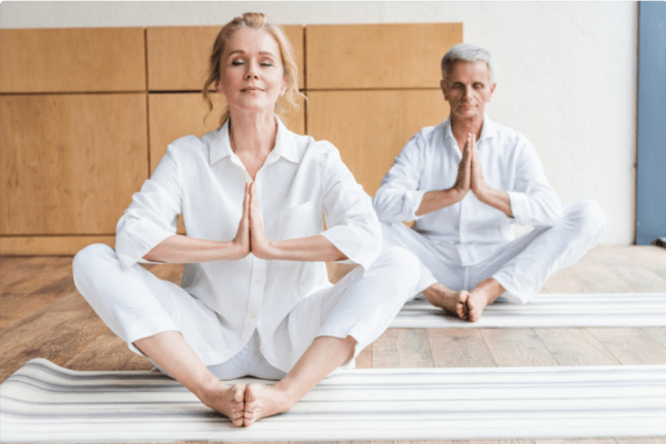two people seated meditating with hands folded and eyes closed