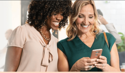 two women looking at a phone screen together
