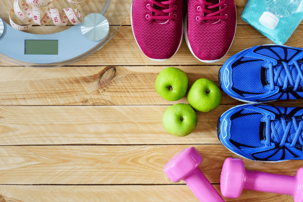 clear glass scale, three green apples, two pink dumbbells, and two pairs of running shoes sitting on wooden floor