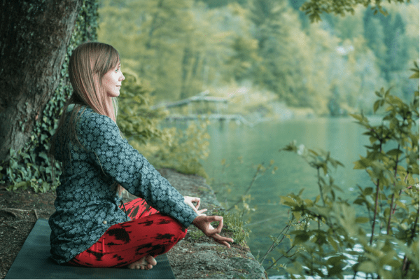woman sitting in meditation pose by the bank of a river