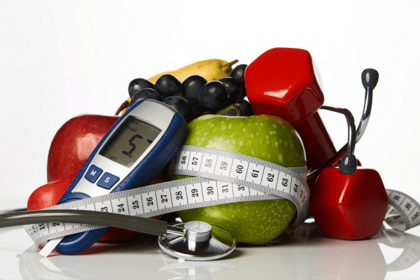 pile of apples, dumbbells, glucometer, and stethoscope, surrounded by measuring tape
