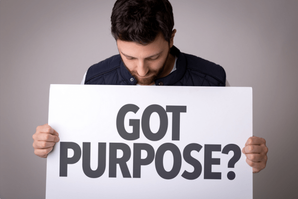 """man holding a sign that says """"got purpose?"""" and looking down at it"""