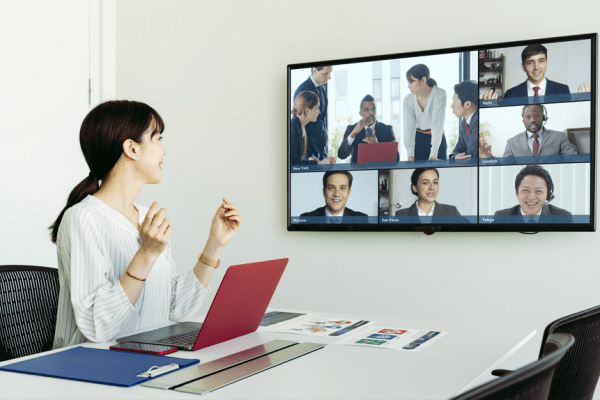 woman sitting at desk with laptop, looking at teleconferencing colleagues on monitor