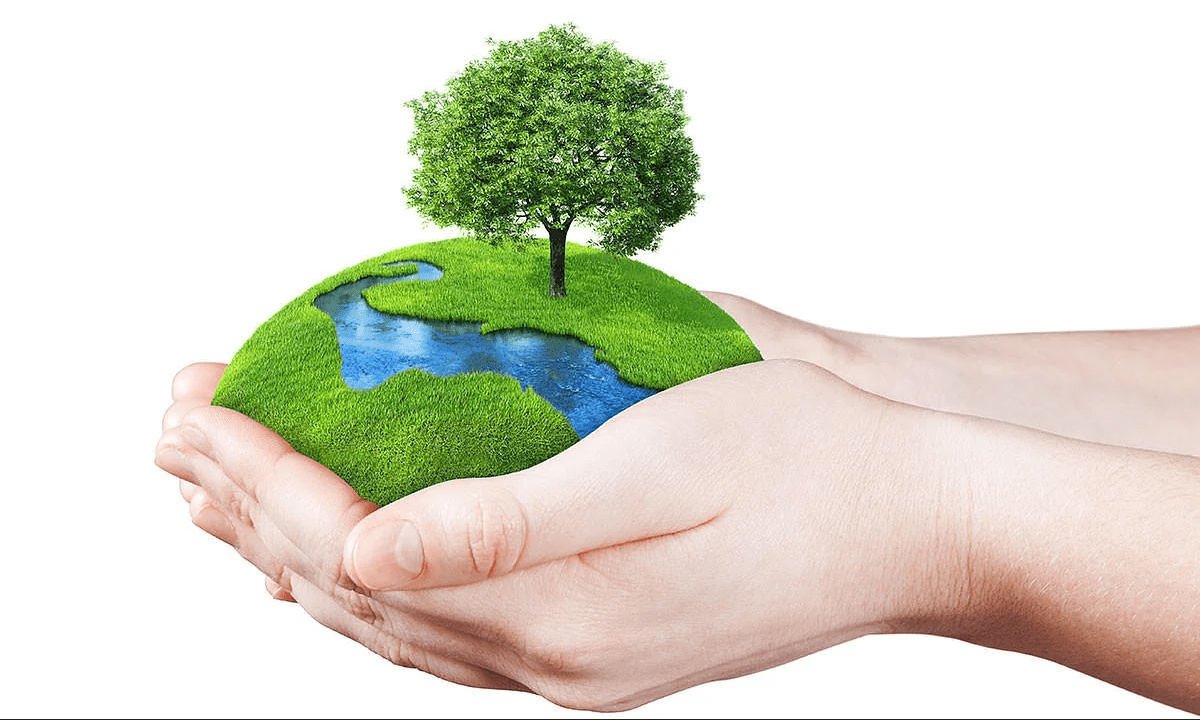 person holding mound of earth with river and tree in hands