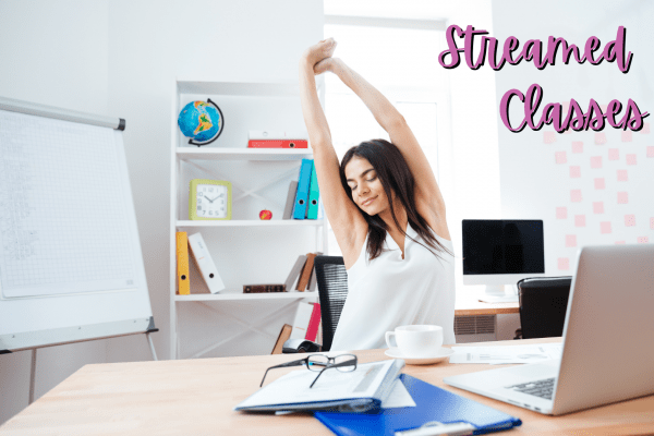 image of woman stretching while seated at her desk